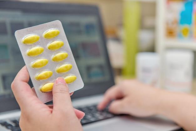 Аптекарь используя компьтер-книжку компьютера в аптеке аптеки или аптеки. рука пакет медицины и ключ рецепт заказа.