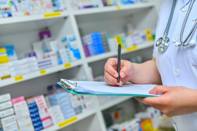Доктор написание рецепта со многими лекарства на полках