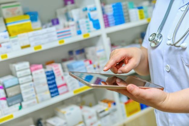 薬局ドラッグストアの棚でディスプレイ上の検索バーにコンピューターのタブレットを使用して医師。オンライン医療の概念。