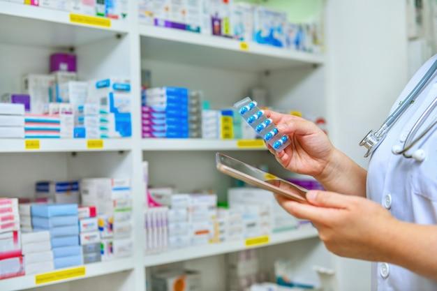 薬局ドラッグストアで処方を充填するための薬カプセルパックとコンピュータータブレットを保持している医師。