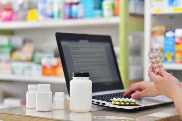 薬局または薬局のドラッグストアでコンピューターのラップトップを使用する薬剤師。薬のパックを持っている手と処方箋のキー。
