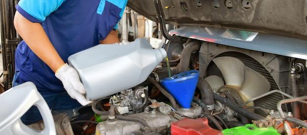 Механик добавляет качественное моторное масло в двигатель. трансмиссия и техническое обслуживание. концепция топлива.
