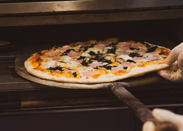 シェフは台所でおいしいピザを準備します