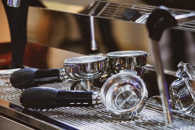 バリスタがコーヒーショップで働いている、バリスタのクローズアップがタンパーを使用して挽いたコーヒーを押す