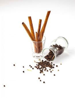 Корица и семена черного перца в стакане, черный перец разбросаны на белом фоне из стеклянной бутылки