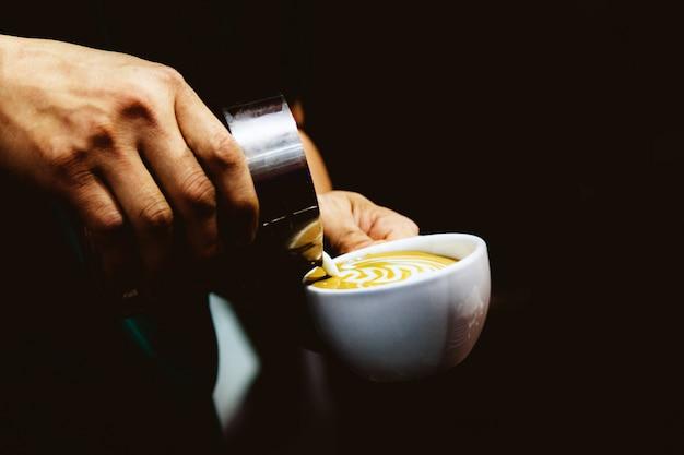 ミルクをコーヒーに注ぐバリスタ