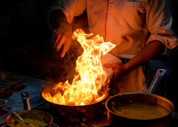 キッチンストーブの上のフライパンで炎で調理するシェフ