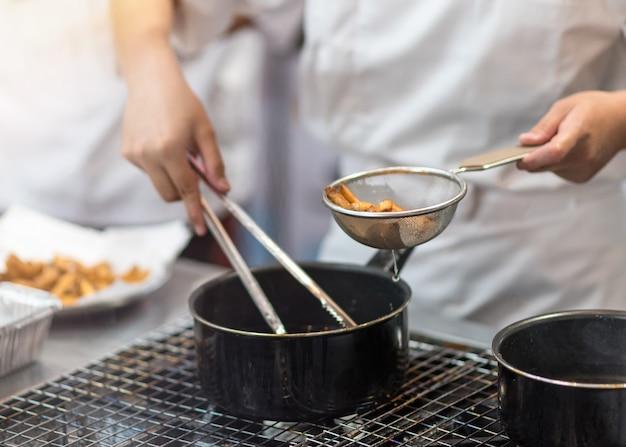 シェフはキッチンでフライドポテトを調理し、おいしいフライドポテトの準備を調理します。