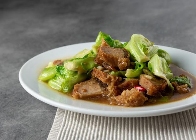 Жареная капуста с хрустящей свининой на тарелке, азиатская еда