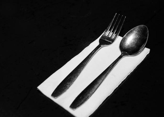レストランのテーブルペーパーでフォークとナイフ、テーブルの場所の設定