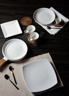 Обед на темном деревянном столе, пустая белая тарелка с вилкой и ложкой