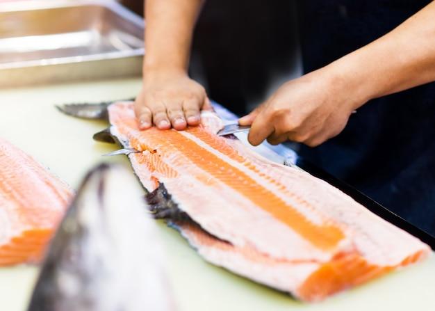 Шеф-повар использует нож для нарезки филе лосося, шеф-повар нарезает лосося в ресторане