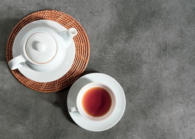 Белая фарфоровая чашка чая и чайник, сервировка стола послеобеденного чая