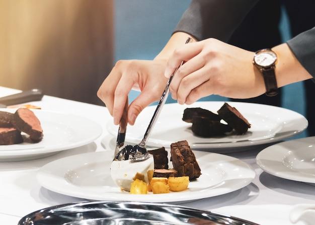 Украсить еду сервировкой блюд к столу в ресторане