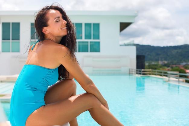 Молодой яркий брюнетка женщина синий купальник расслабляющий