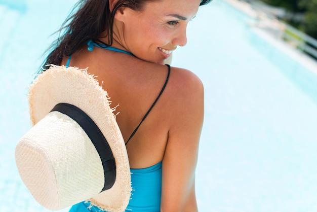 Счастливая брюнетка загорелая женщина в синем купальнике