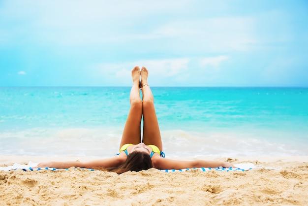 細い足を伸ばして横になっている若い日焼け女性