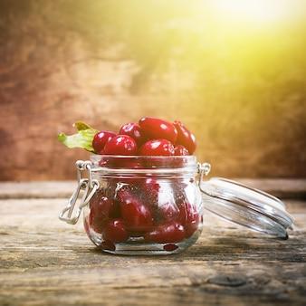小さなガラスの瓶に熟した赤いコーネルベリー