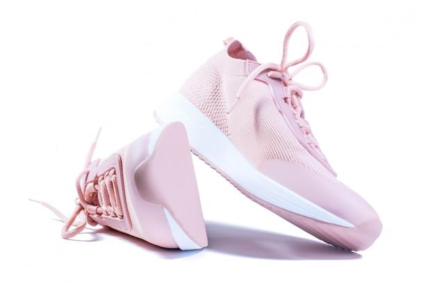 白で隔離されるピンクのスポーツシューズ