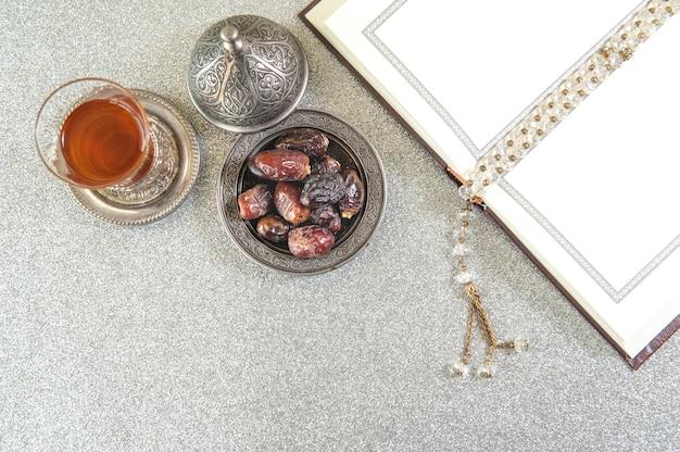 イスラムのクルマ、ラマダン、デートのヤシの果物と金属の皿に置かれた茶