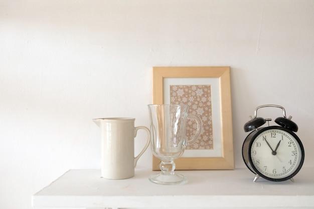 黒い目覚まし時計の花瓶とテーブルの上のガラス