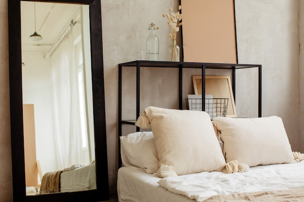 Кровать с подушками и красивым постельным бельем теплых тонов