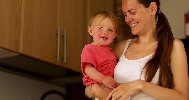 若い母親が彼女の腕に幸せな赤ちゃんを保持していると台所でカメラを見て