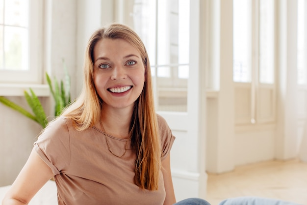 カメラを見て明るい部屋に座っている広い笑顔で幸せなカジュアルな成人女性
