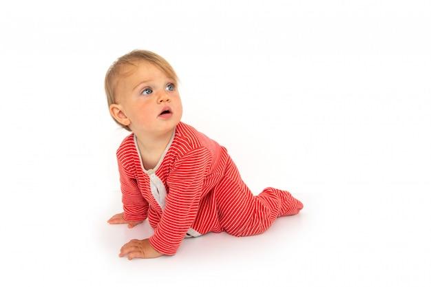 Очаровательная голубоглазая малышка в красном комбинезоне ползет на четвереньках и удивленно отводит взгляд