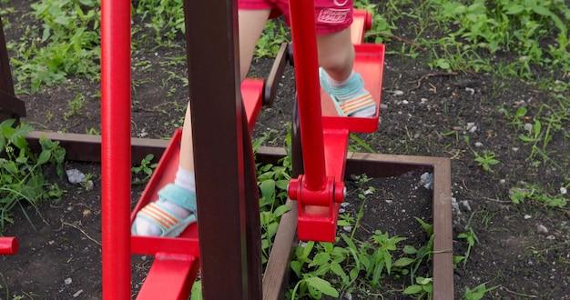 子供の遊び場で運動をしている子供の足のクローズアップ