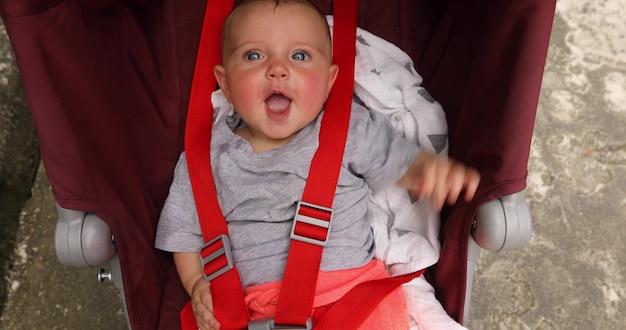 屋外のベビーカーで少し愛らしい、好奇心が強い赤ちゃん