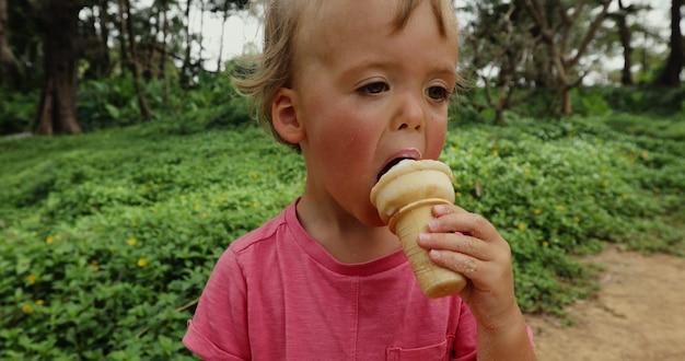 アイスクリームを食べるかわいい幼児男の子。アイスクリームを食べる汚れた顔を持つ子供