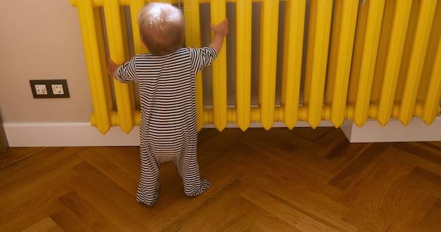 Вид сзади неузнаваемого малыша в полосатых гусеницах касаясь желтой теплой батареи возле стены дома