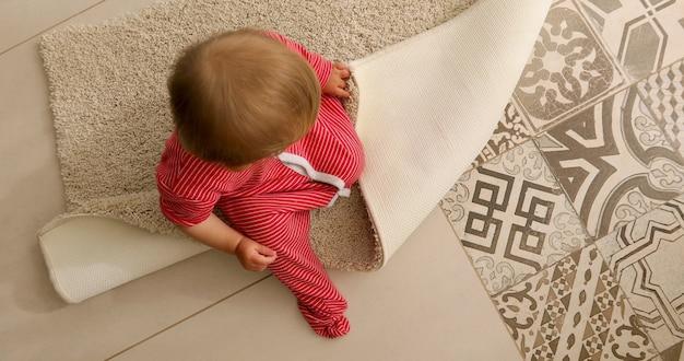 座っていると自宅でカーペットに触れる赤い縞模様のロンパースで認識できない赤ちゃんの上から