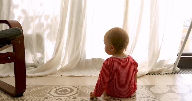 Вид сзади до неузнаваемости малыша в красный полосатый комбинезон сидит на полу и смотрит в окно с занавесками у себя дома