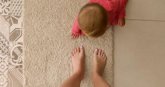 Вид сверху неузнаваемого ребенка в красных ползунках, сидящих на мягком ковре на полу рядом с обрезанными голыми ногами матери