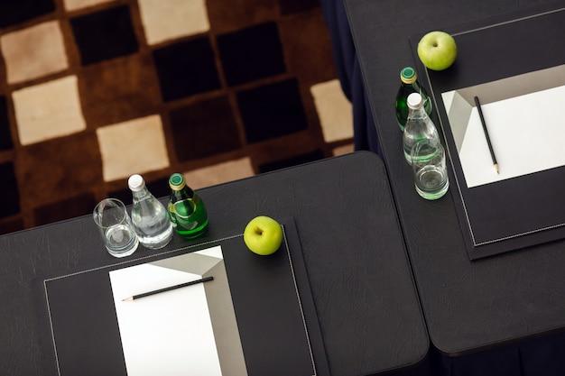 Расположенные парты с водой и яблоком рядом с канцелярскими товарами в классе