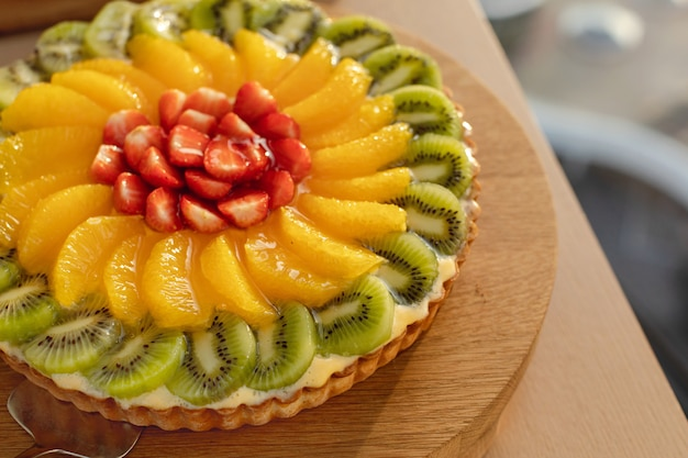 Красочный украшенный фруктовый торт на деревянной тарелке