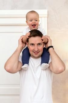 Довольный мужчина с жизнерадостным малышом на плечах