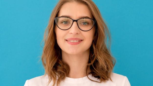 Молодая женщина надевает очки