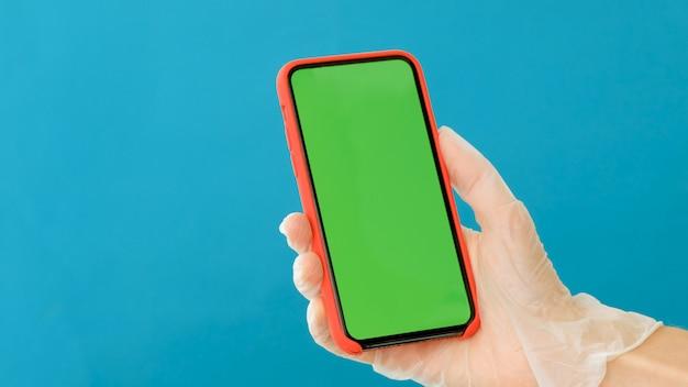 Рука в резиновой перчатке держит смартфон с зеленым экраном