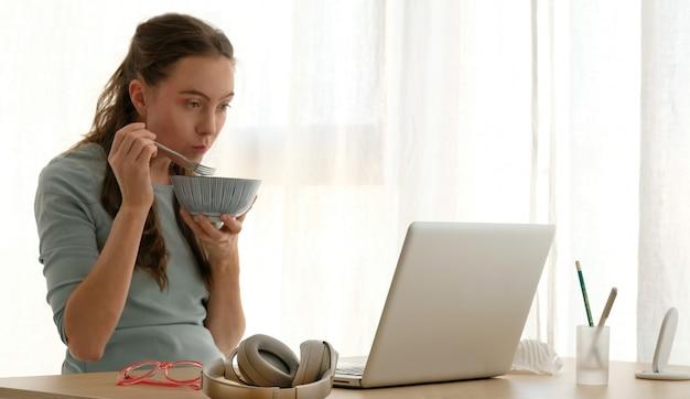 Молодая женщина ест кашу за столом в гостиной