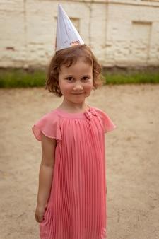 ピンクのドレスと夏の日の誕生日のお祝いの間に砂浜の遊び場に立っている間笑顔でパーティーハットのかわいい女の子