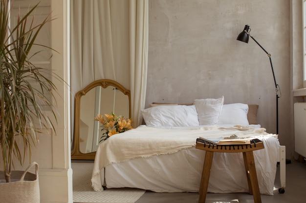空のベッドと雑誌のコピースペースとコーヒーテーブルのある居心地の良いベッドルーム