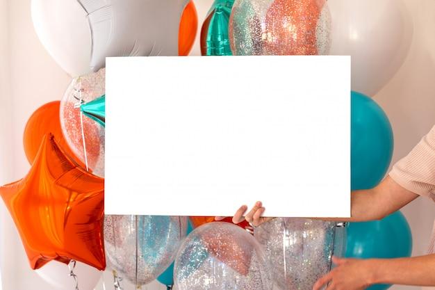 風船で部屋のポスターを持つ女性