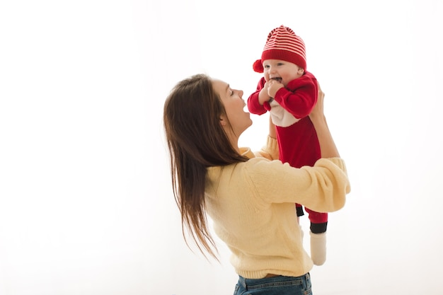 Женщина, держащая очаровательного малыша в праздничном костюме