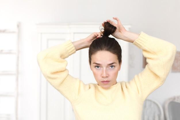 カメラを見て髪型を作るカジュアルな女性