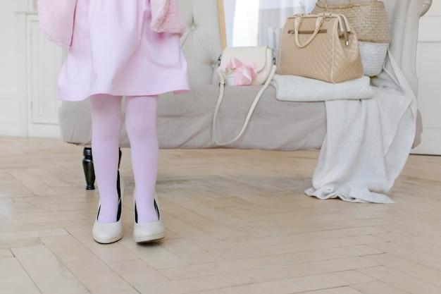 Маленький ребенок, играющий с мамой на высоких каблуках