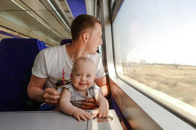 彼の小さな息子と列車で旅する男の子の父