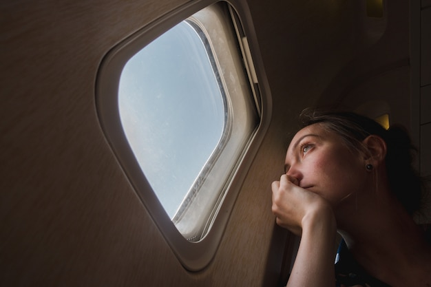 Грустная женщина в иллюминаторе в самолете